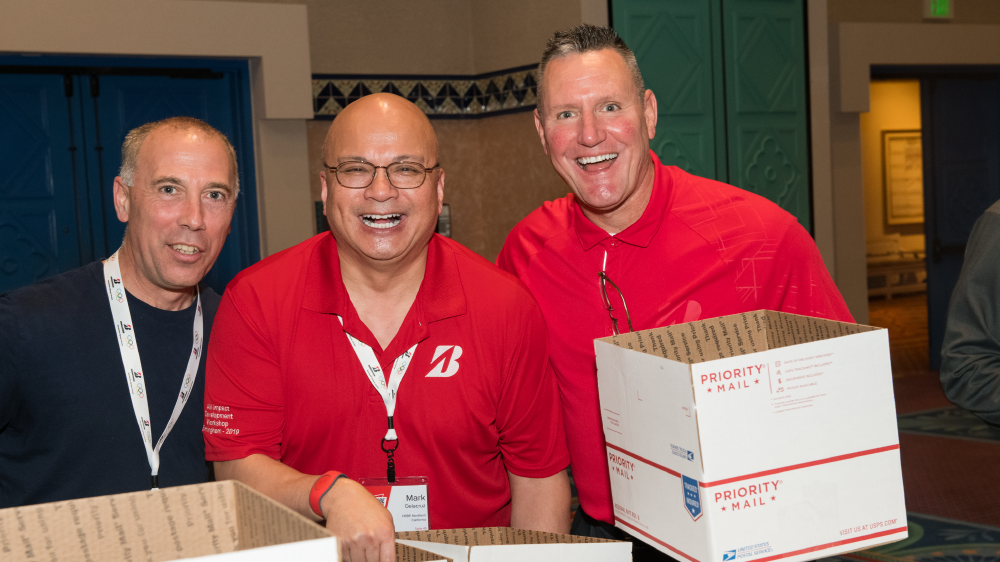 Derek Sanders, Region Operations Manager; Mark Delacruz, HRBP; and Joe Venezia pack a box  for the troops as part of the BSRO give back program at the 2020 National Leadership Conference